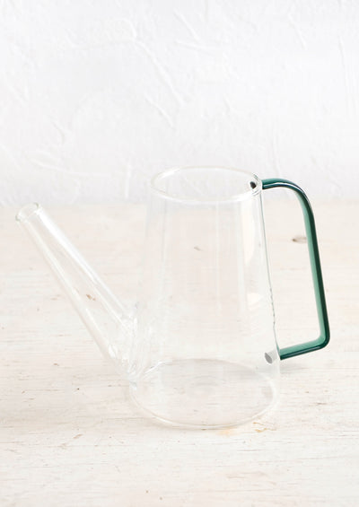 Clear glass watering can with angular, green tinted glass handle