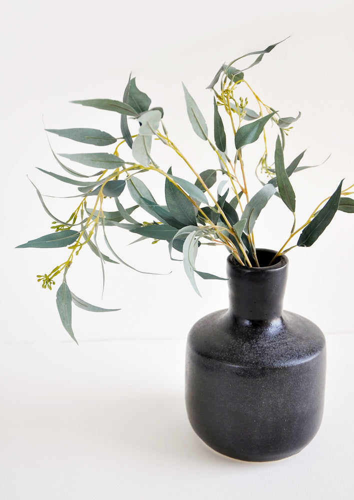 2: Glossy black ceramic vase with wide base and narrow opening, displayed with eucalyptus branch