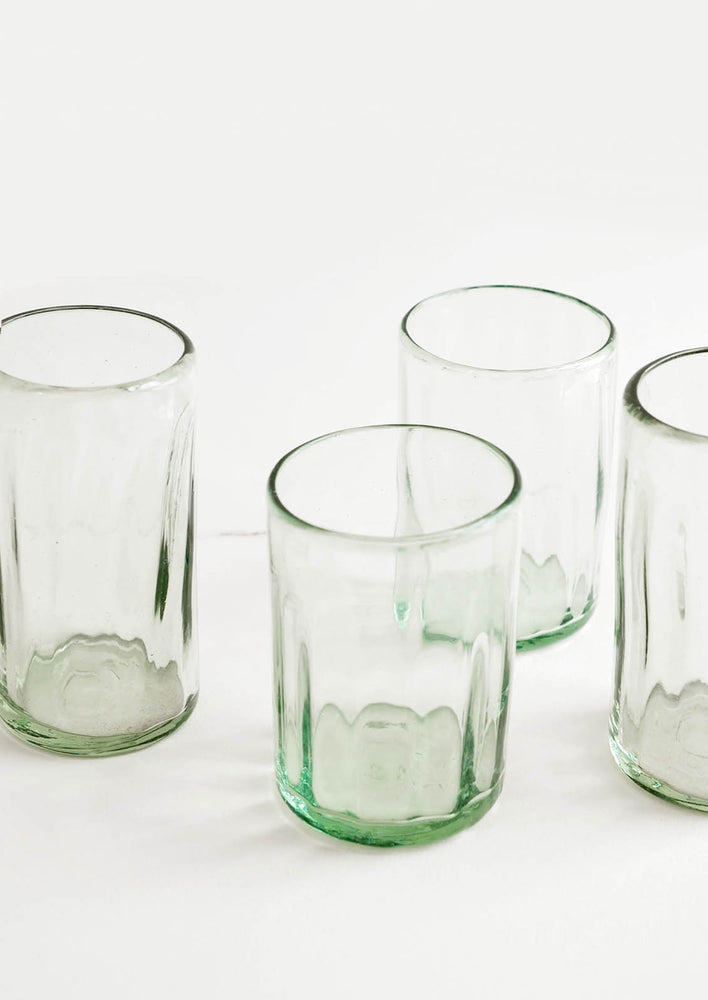 2: Four horizontally ribbed tumblers in thick green hued glass.