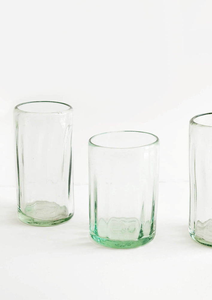 1: Three horizontally ribbed tumblers in thick green hued glass.