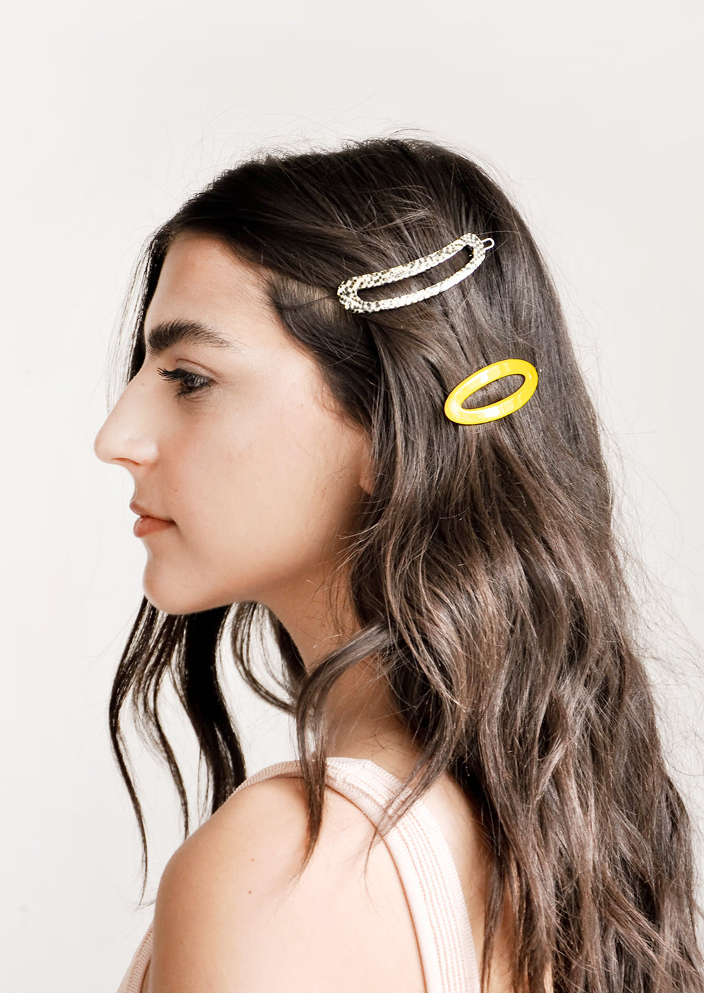 5: Two oval hair clips, one yellow and one white, shown on model