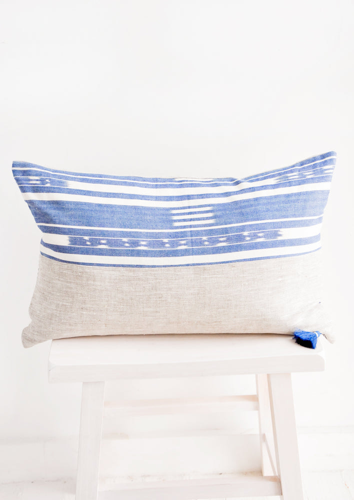 Rectangular pillow in two fabrics, top half is blue and white pattern, bottom half is natural linen