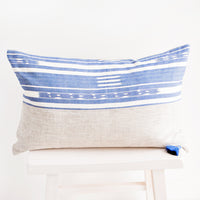 1: Rectangular pillow in two fabrics, top half is blue and white pattern, bottom half is natural linen