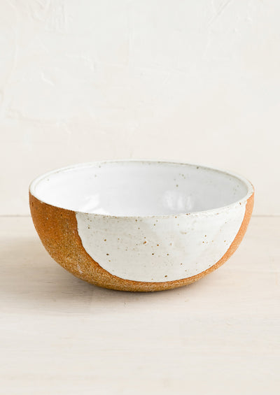 A ceramic bowl in sandy clay with speckled white half moon design.