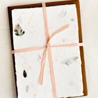 2: Handmade flower petal paper and kraft envelopes bound with peach ribbon.