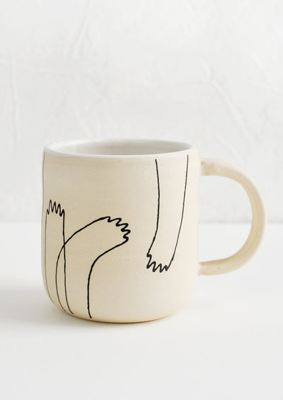 An ivory clay ceramic mug with hand drawn imagery of creature-like hands.