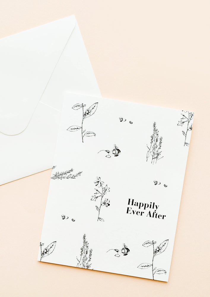 "1: Notecard with black botanical drawings on white background and the text ""Happily Ever After"", with white envelope."