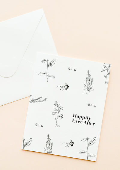 "Notecard with black botanical drawings on white background and the text ""Happily Ever After"", with white envelope."