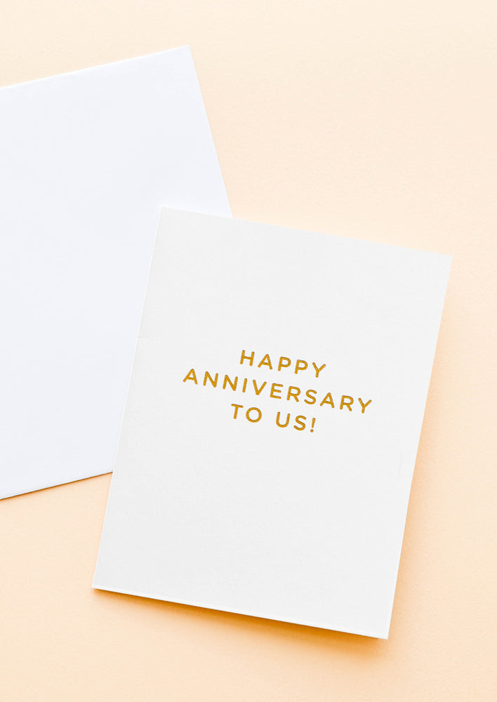 "1: A pale gray greeting card with gold foil text reading ""happy anniversary to us."""