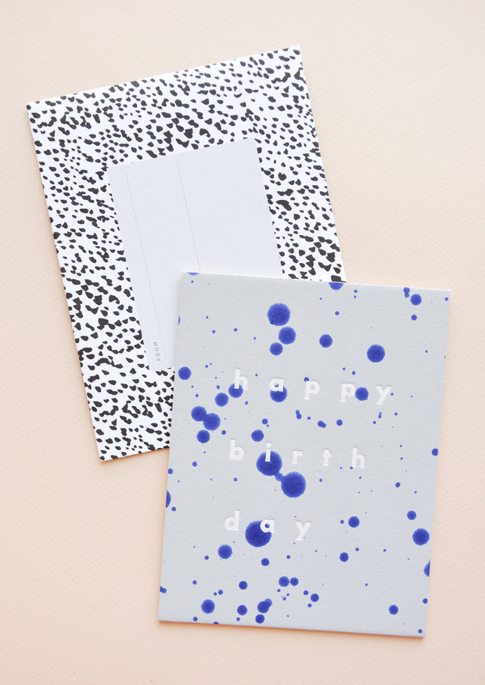 "1: Light blue notecard with dark blue paint splotches and the text ""happy birthday"" and black and white spotted envelope."