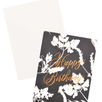 "3: Notecard with white flowers on black background and the text 'Happy Birthday"" in metallic script, with white envelope."