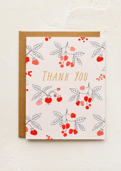 "A greeting card with raspberry print and ""Thank you"" gold lettering."