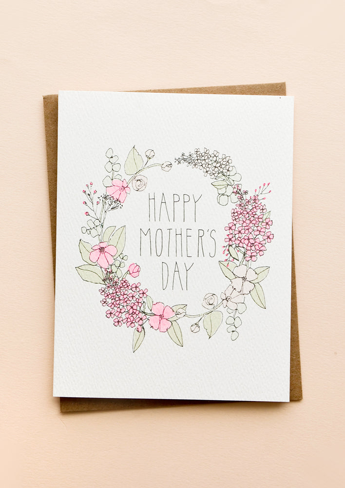 "1: Greeting card with illustrated floral wreath and ""Happy Mother's Day"" printed in center"