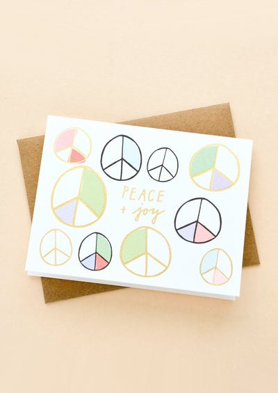 "Greeting card with colorful peace signs and text at middle reads ""Peace + joy"""