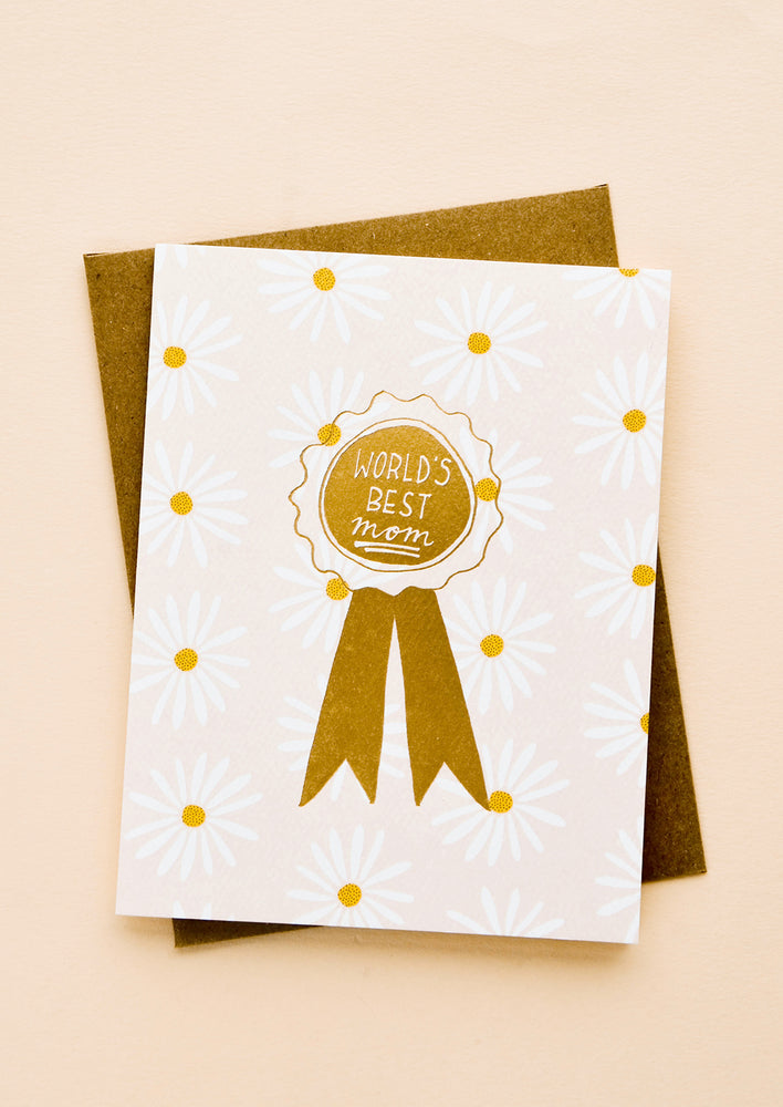 "2: Greeting card with allover daisy pattern and gold ribbon reading ""World's Best Mom"""