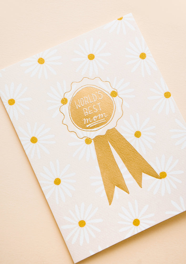 "1: Greeting card with allover daisy pattern and gold ribbon reading ""World's Best Mom"""