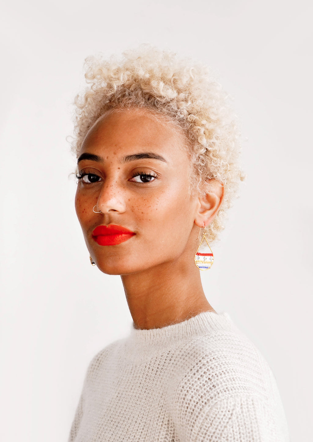 2: Model wears teardrop shaped gold and glass bead earrings.
