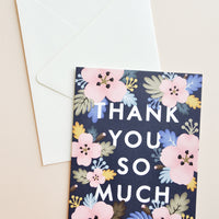 "1: Black notecard with pastel Hawaiian floral decoration and the text ""Thank you so much"" with white envelope."
