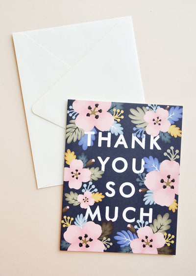 "Black notecard with pastel Hawaiian floral decoration and the text ""Thank you so much"" with white envelope."
