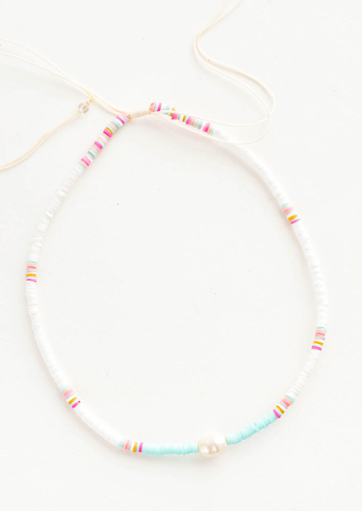 White / Aqua: Necklace made from disc-like, pastel plastic beads with a single pearl in middle