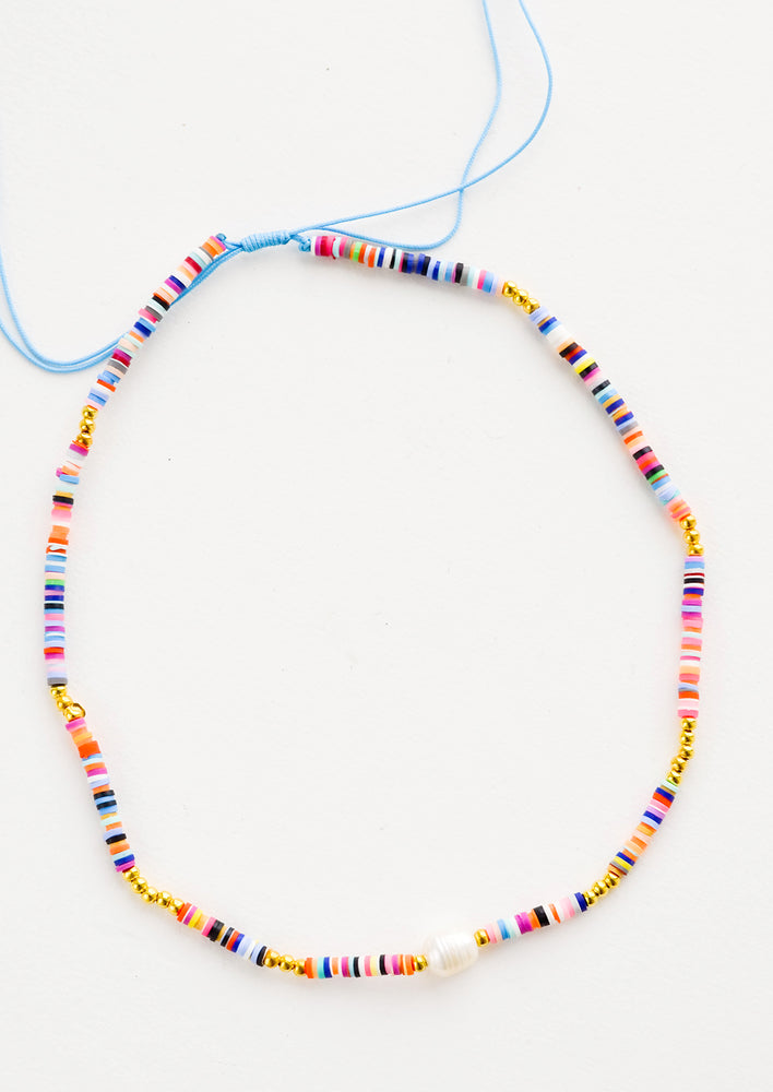Multicolor: Necklace made from disc-like, multicolored plastic beads with a single pearl in middle