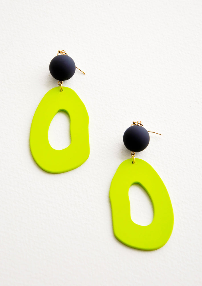 Lime / Navy: Dangling earrings featuring asymmetric lime green cut out oval hanging from black bead.