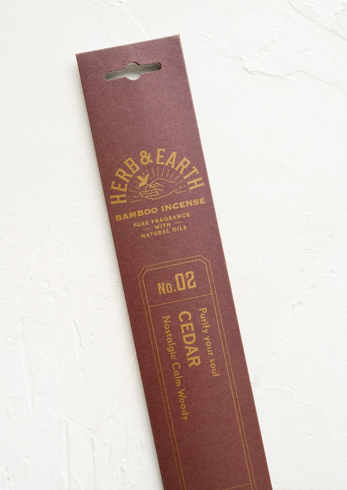 A brown packaging sleeve containing cedar scented incense.