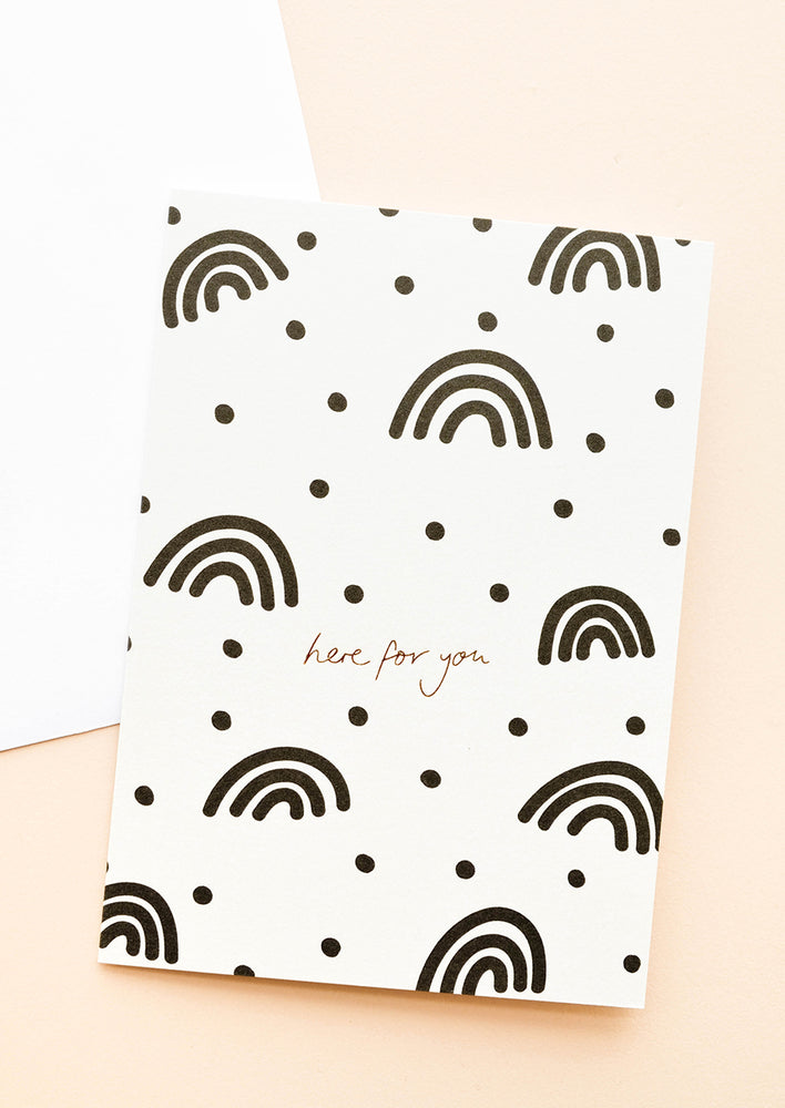 "White greeting card illustrated with black rainbows, polka dots, and the words ""here for you"" in gold foil."