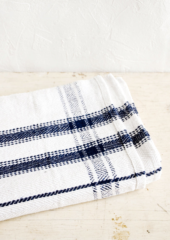 1: Folded cotton tablecloth in white with navy blue stripe detail
