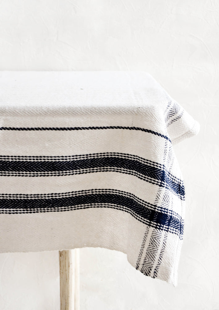 2: White cotton tablecloth with navy blue stripes displayed on a table