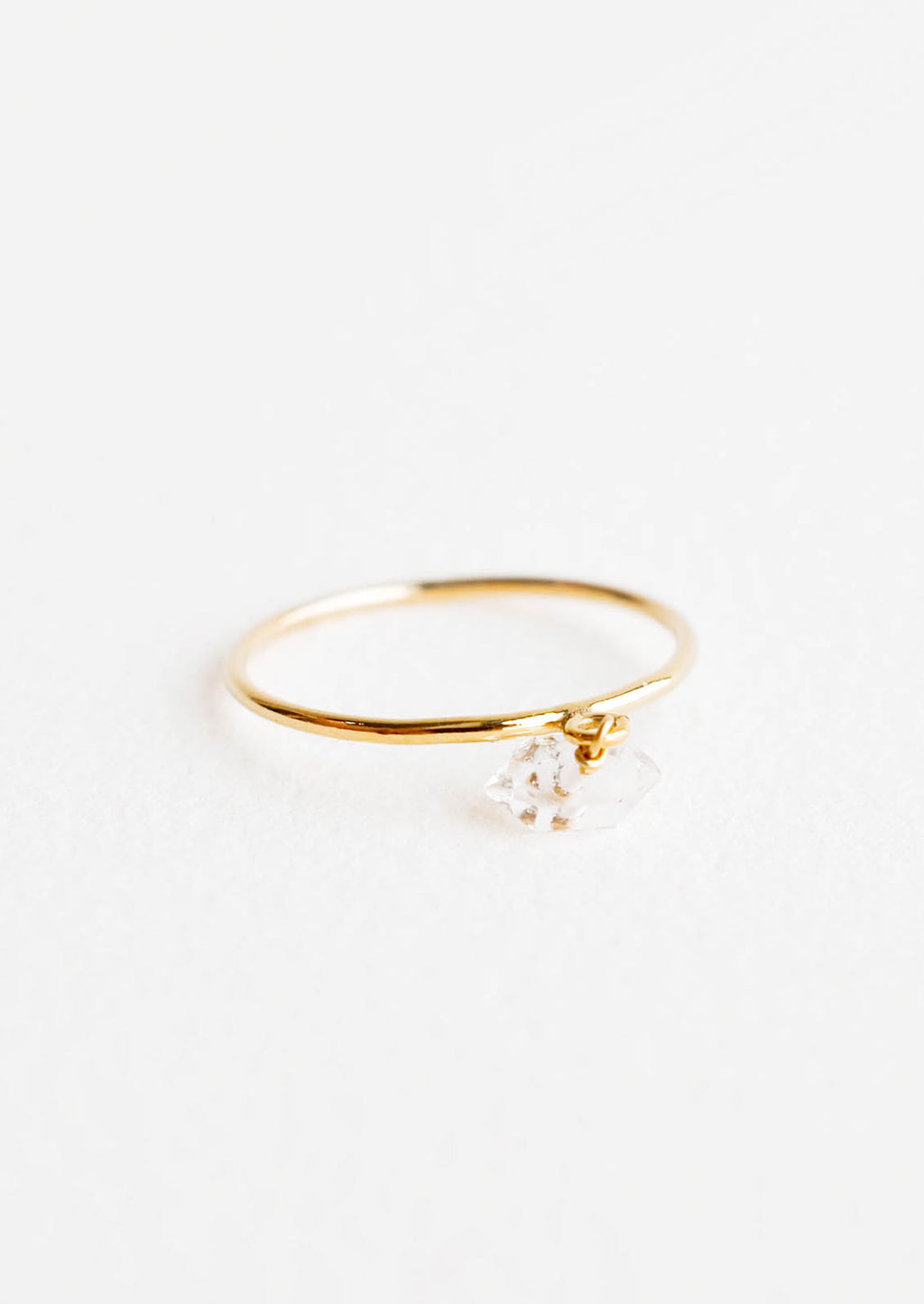 1: Slim yellow gold ring with a dangling white faceted stone.