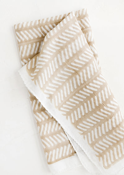 Lightweight cloth napkin with beige background and white herringbone block print pattern