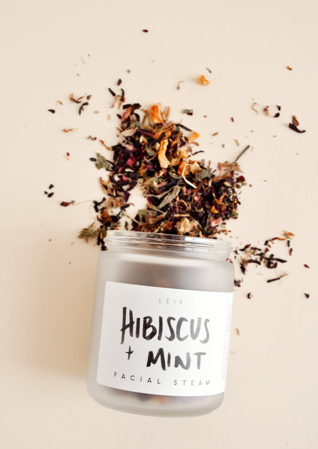 1: A small frosted glass jar with a black and white label spilling out a mix of dried flowers.