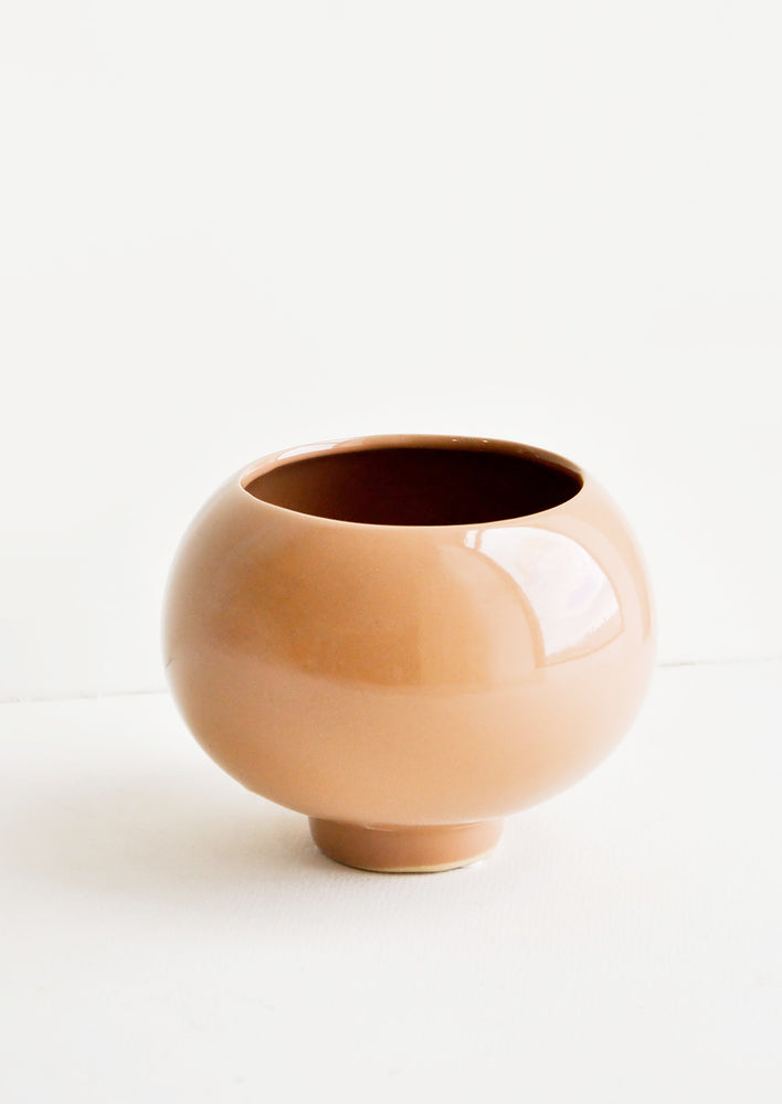 1: A ceramic planter in round shape with footed base and a glossy cocoa brown finish.