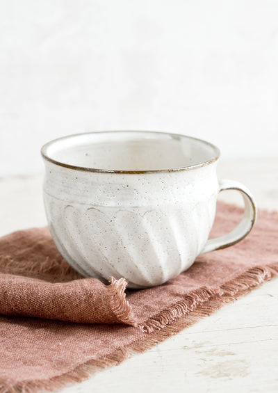 A wide ceramic mug with handmade fluting detail.