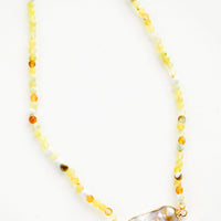 1: Beaded necklace with round gemstone beads in variegated lemon yellow, asymmetrically shaped grey pearl pendant at front and center