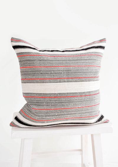 Square throw pillow in natural tan color with black and red variegated stripes