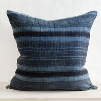 1: A square throw pillow in indigo fabric with variegated black stripes.