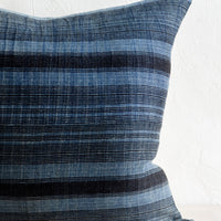 2: A throw pillow in indigo fabric with variegated black stripes.