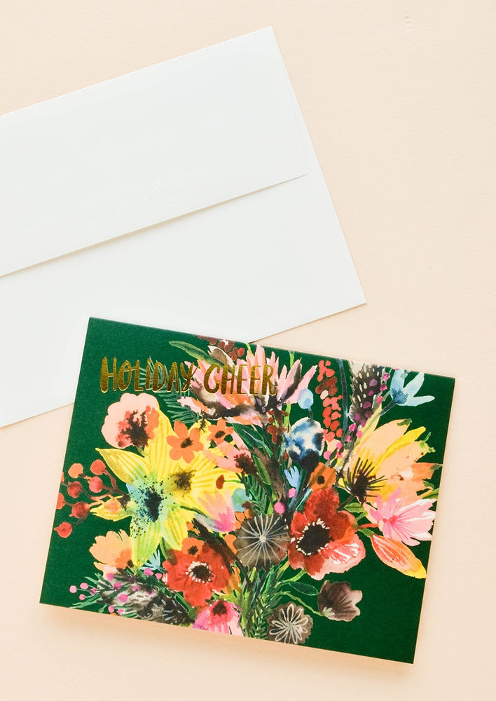 "Greeting card with elaborate, colorful floral bouquet with ""Holiday cheer"" printed in gold letters. Shown with white envelope."