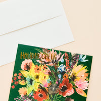 "1: Greeting card with elaborate, colorful floral bouquet with ""Holiday cheer"" printed in gold letters. Shown with white envelope."