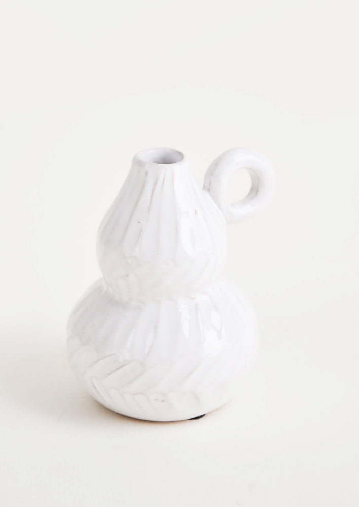 1: White ceramic bud vase with pinched center and tapered top. Small, round handle at side. Allover etched texture.
