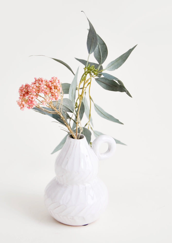 2: A small white ceramic vase with textured detailing, displaying a floral arrangement.
