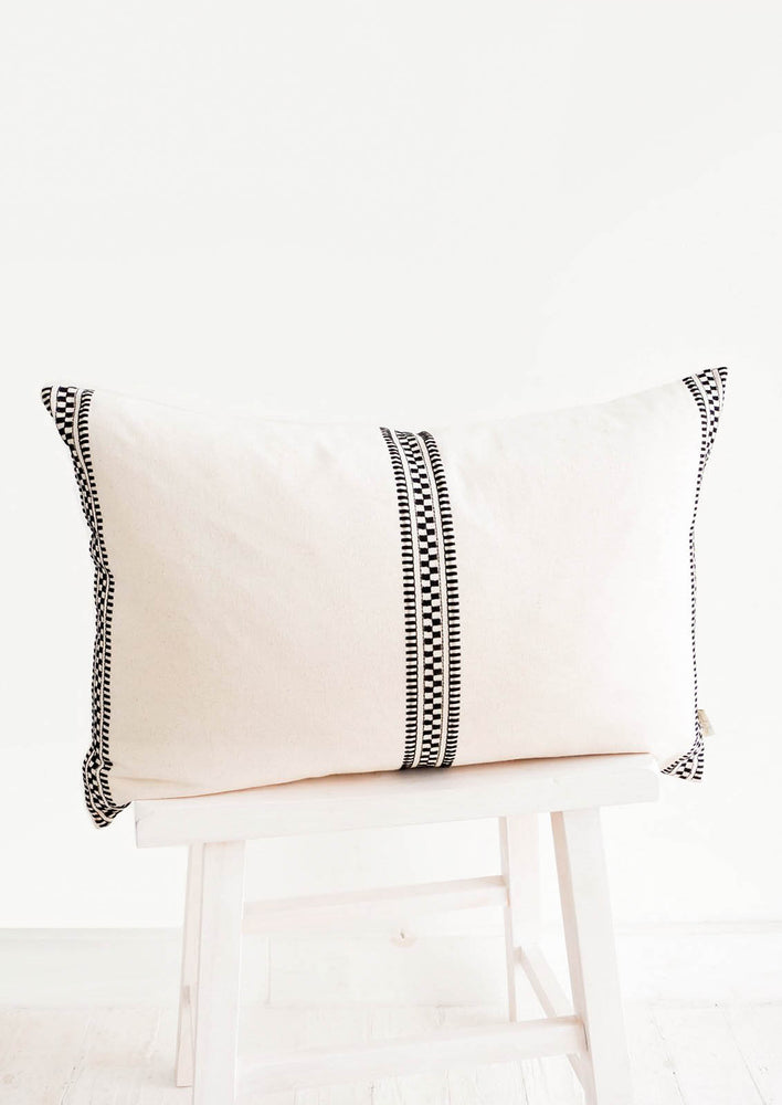 1: Rectangular throw pillow in natural cotton canvas with black geometric embroidered vertical stripes at sides and center
