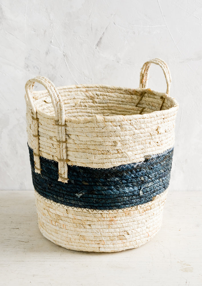 1: A storage basket with two top handles, woven from natural fiber.