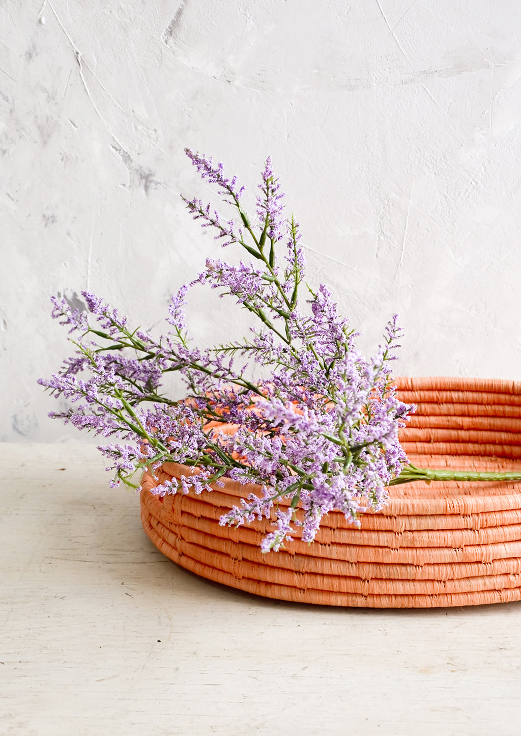 2: Woven raffia basket in peach color, housing purple flowers.