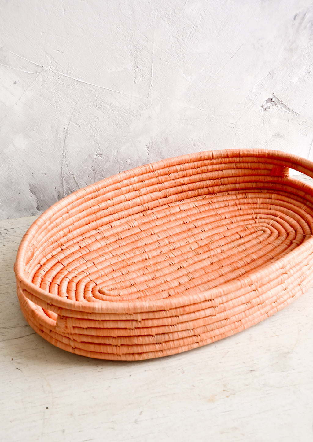 1: Oval shaped, shallow basket woven in peach raffia with cutout handles at sides.