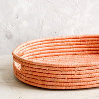 4: Oval shaped, shallow basket woven in peach raffia with cutout handles at sides.