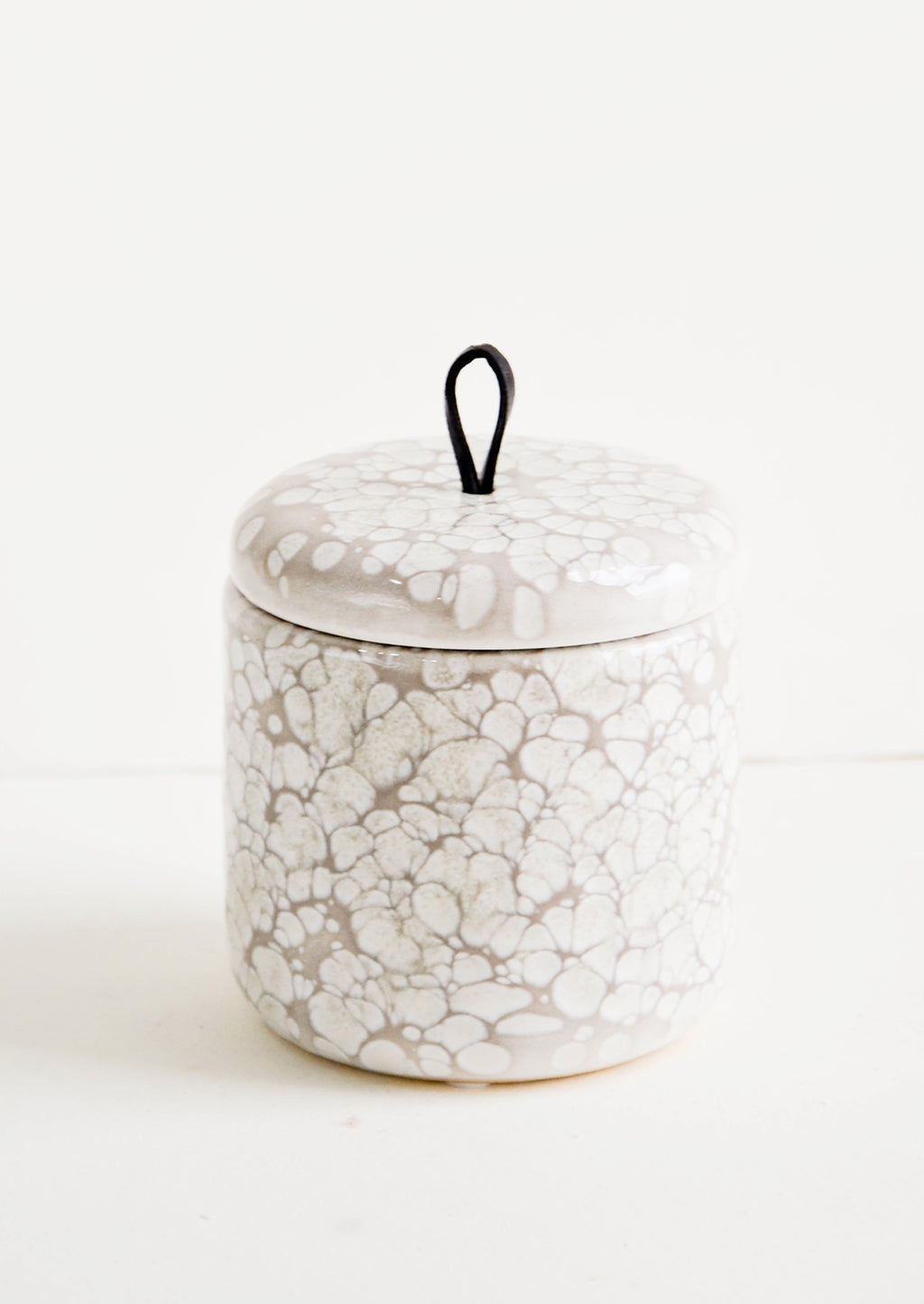 2: Ceramic storage jar in bubbly, glossy grey glaze with black leather pull on lid
