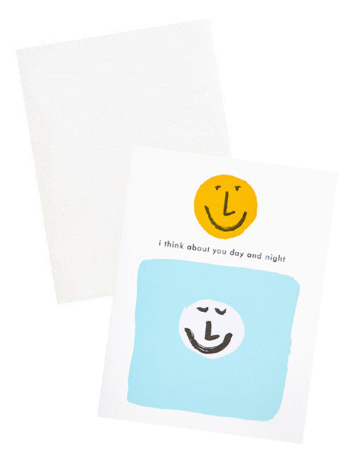 "2: White greeting card with black ""I think about you day and night"" text. Two smiley faces, one white and one yellow. Shown with envelope."